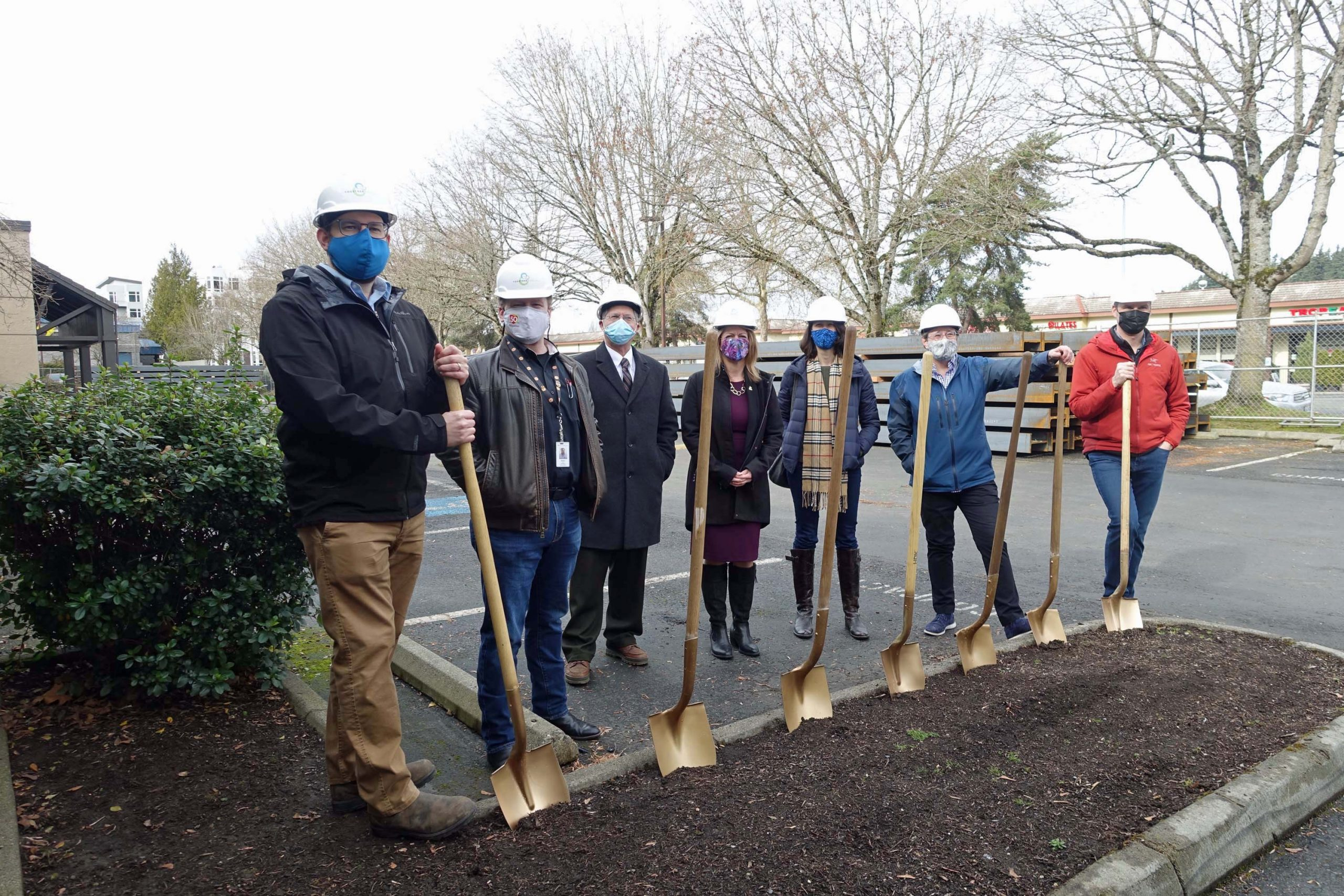 Outside photo of seven adult individuals all holding golden shovels, breaking ground at Together Center, February 2021.